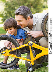 Father and son fixing bike - Side view of father and son...