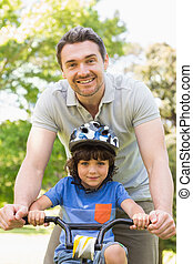 Man teaching his son to ride a bicycle - Portrait of a...