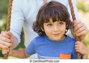 Close-up of a father pushing cute boy on swing