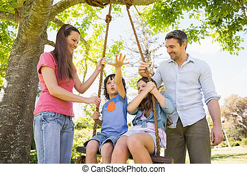 Happy couple pushing kids on swing
