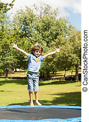 Happy boy jumping high on trampoline in the park - Full...