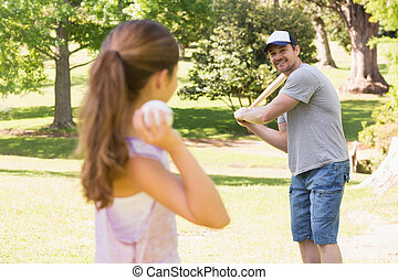 Father and daughter playing baseball in the park