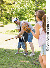 Family playing baseball in park - Family of three playing...