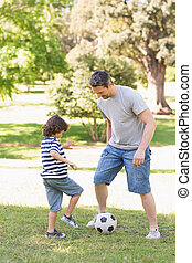 Father and son playing football in the park - Full length of...