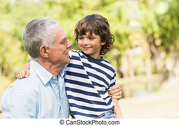 Grandfather and son smiling in the park