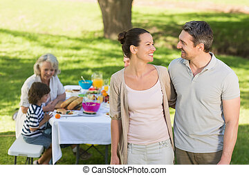 Couple with family dining at outdoor table - Couple with...