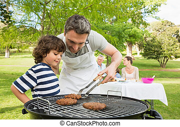 Family on vacation having barbecue - Man and son barbecuing...