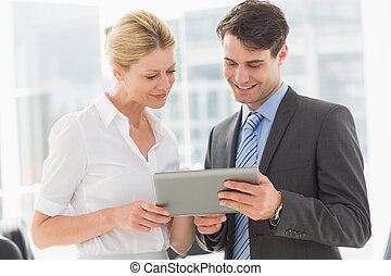 Business team looking at tablet pc together in the office