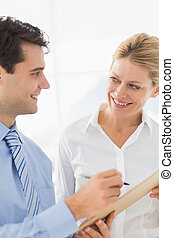 Happy business team working from clipboard together in the...