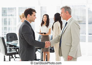 Businessmen meeting and shaking hands in the office