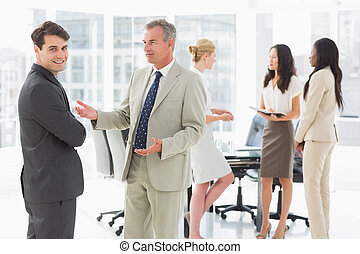 Business people talking together in conference room in the...