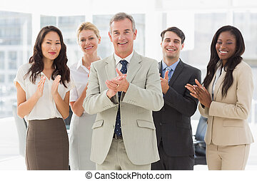 Business team standing and clapping at the camera in the...
