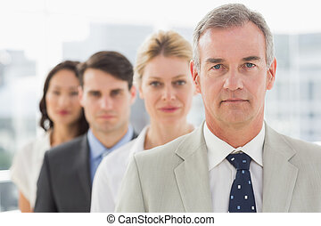 Stern business team standing in a line in the office