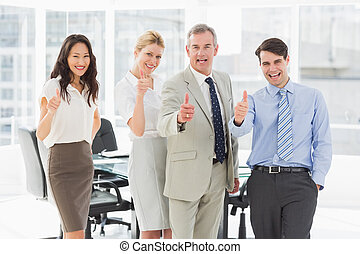 Business team giving thumbs up to the camera in the office