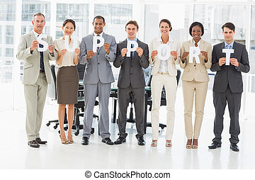 Happy business team holding up letters spelling support in...