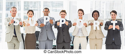 Diverse business team holding up letters spelling support in...