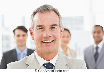 Mature businessman smiling at camera with team behind him in...