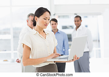 Pretty Asian businesswoman using laptop with team behind her...
