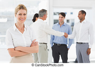 Blonde businesswoman with team behind her smiling at camera