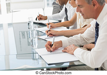 Business people taking notes at a meeting in the office