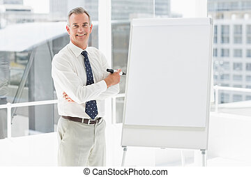 Smiling businessman standing at whiteboard with marker in...