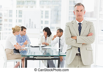 Serious businessman looking at camera while staff discuss behind him in the office