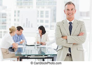 Happy businessman looking at camera while staff discuss...