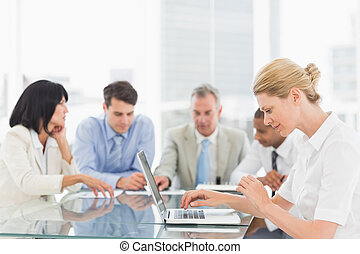Businesswoman using her laptop during a meeting in the...
