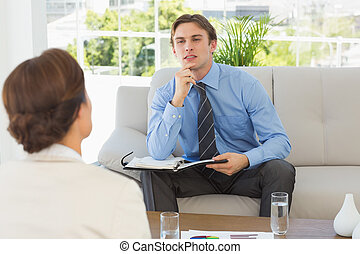 Young businessman listening to colleague sitting on couch in...