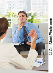 Young businessman listening to female colleague sitting on...