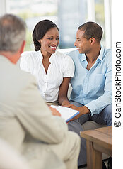 Young couple interacting with salesman on the couch