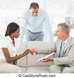 Salesman handing pen to client to sign the contract in the...