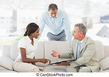 Salesman showing clients where to sign the contract in the...