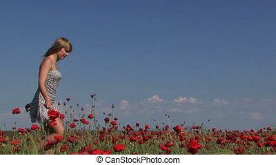 In a poppy field - Young woman with a bouquet of poppies...