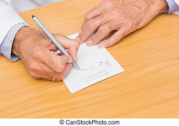 Doctor sitting at his desk writing on prescription pad in...