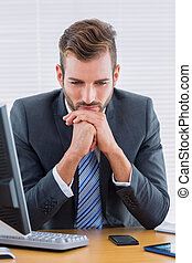 Thoughtful businessman sitting at office desk - Young...