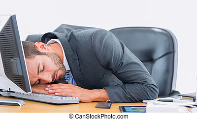Businessman resting with head over keyboard at desk - Young...