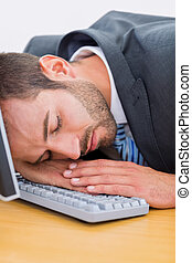 Businessman resting with head over keyboard at desk -...