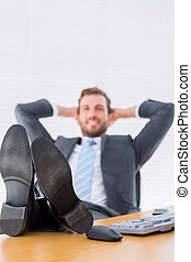 Relaxed businessman sitting with legs on desk - Full length...
