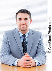 Smiling confident businessman at office desk - Portrait of a...