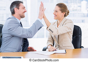 Smartly dressed colleagues giving high five in business...
