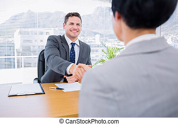 Executives shaking hands after a business meeting - Smartly...