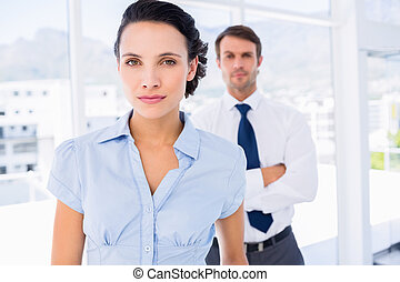 Serious businesswoman with male colleague in background -...