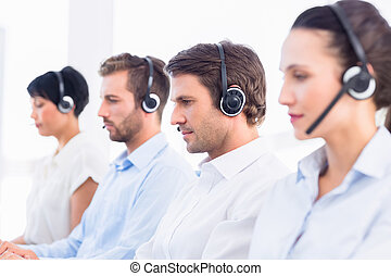 Group of business colleagues with headsets in a row - Side...