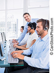 Manager and executives with headsets using computers - Side...