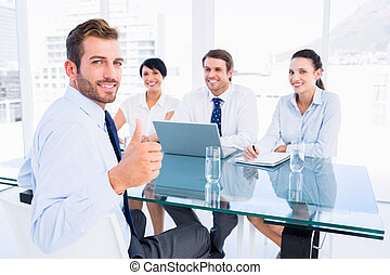 Executive gesturing thumbs up with - Portrait of an...
