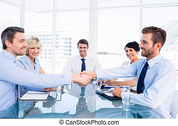 Executives shaking hands during business meeting at office...
