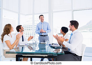 Executives clapping around conference - Business executives...