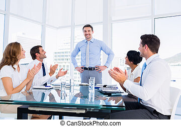 Executives clapping around conference table - Business...