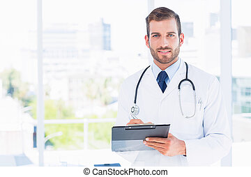 Portrait of a confident male doctor with clipboard standing...